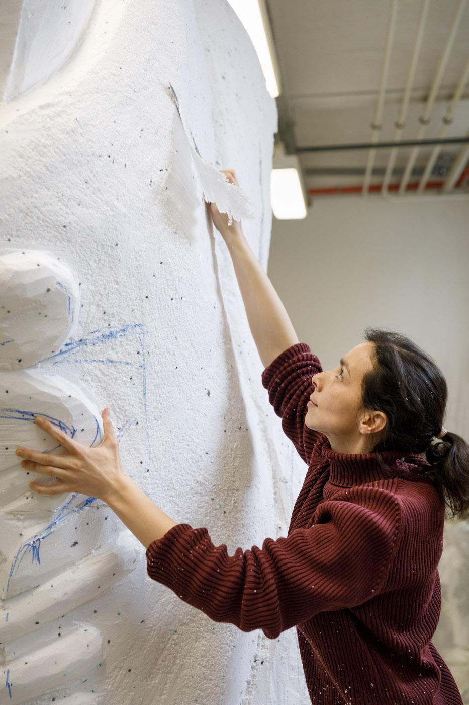 Bildhauerin bei der Arbeit Styroporskulptur Schnitzen Messer